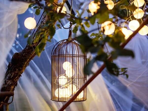 Invista em gaiolas decorativas com pisca pisca para festa noturna
