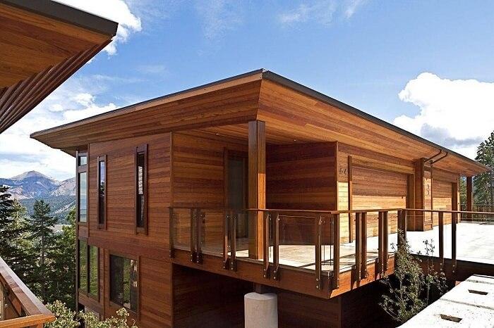 Guarda corpo de madeira e vidro complementa a decoração dessa casa de veraneio