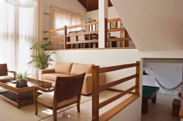 Guarda corpo de madeira utilizado dentro dessa residência se harmoniza com a decoração