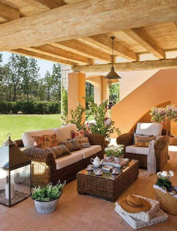 Móveis rústicos e flores encantam a decoração dessa varanda de madeira
