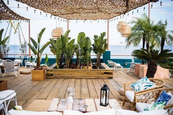 Móveis rústicos e vasos com folhagens complementam a decoração dessa varanda de madeira