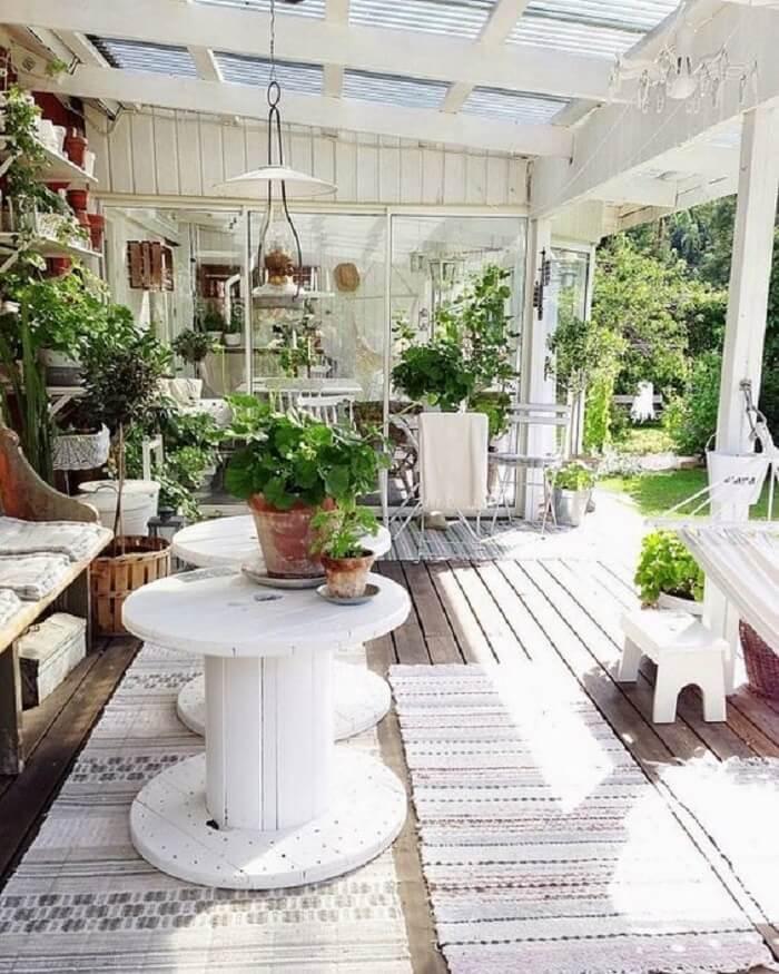 Mesa de centro em forma de carretel complementa a decoração da varanda de madeira