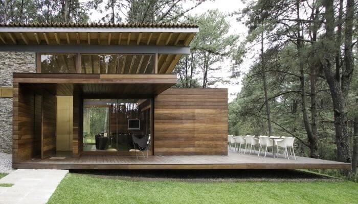 Mobiliário metálico branco e varanda de madeira