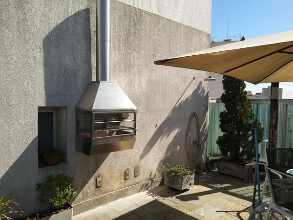 Modelo de churrasqueira de parede com laterais de vidro e coifa de inox