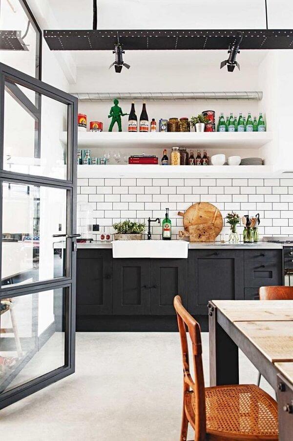 O azulejo branco da cozinha realça os móveis escuros do espaço