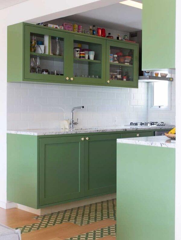 O azulejo branco realça o verde oliva dos armários da cozinha