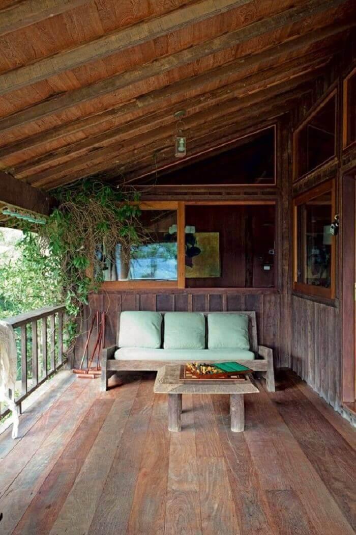 O sofá de três lugares com tecido verde complementa a decoração da varanda de madeira