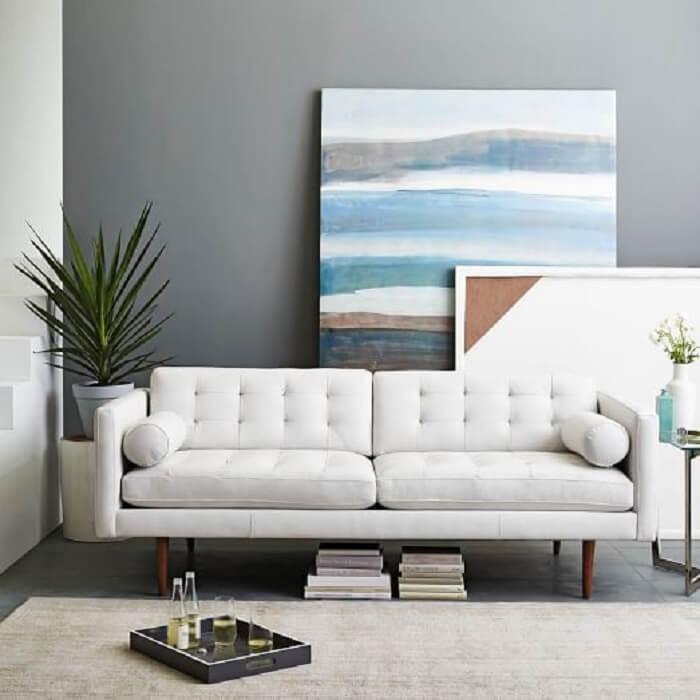 O tecido de sofá de couro em tom branco traz neutralidade para a decoração