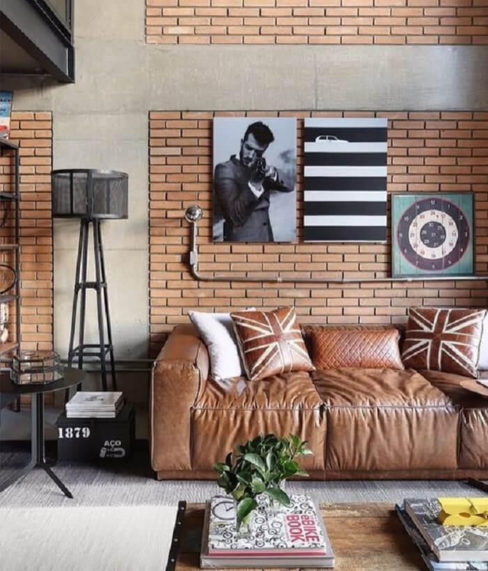 O tecido para sofá de couro em tom caramelo se harmoniza com os tijolinhos da parede