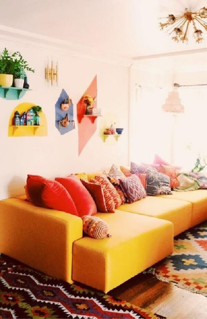 O tecido para sofá na cor amarela se conecta com as almofadas coloridas