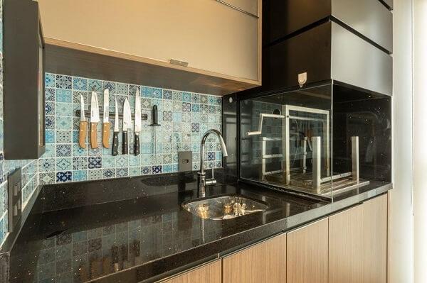 Parede de ladrilho hidráulico azul, bancada preta e churrasqueira com lateral de vidro