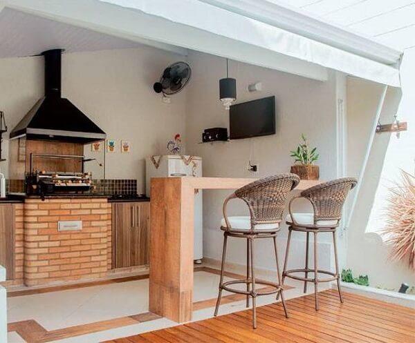 Pequena área gourmet conta com churrasqueira de vidro pré-moldada com base de tijolinhos