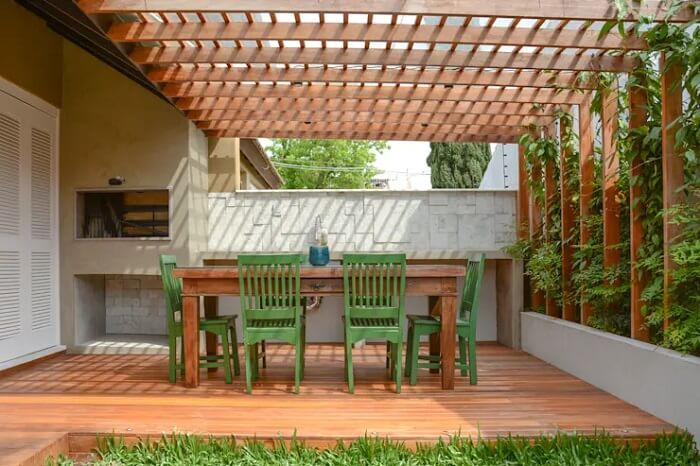 Pergolado na varanda de madeira com mesa de seis lugares