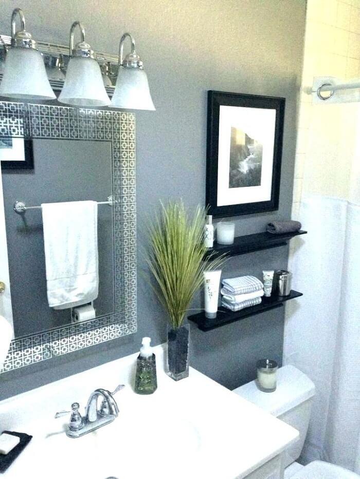 Prateleira para banheiro na cor preta se harmoniza com a moldura do quadro