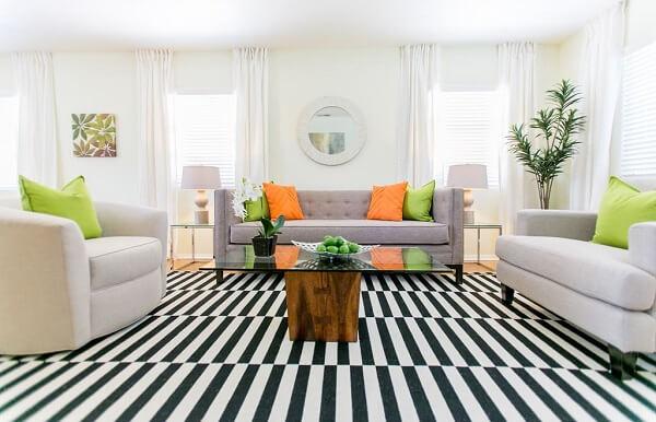 Sala de estar clean com almofadas coloridas e tapete listrado preto e branco