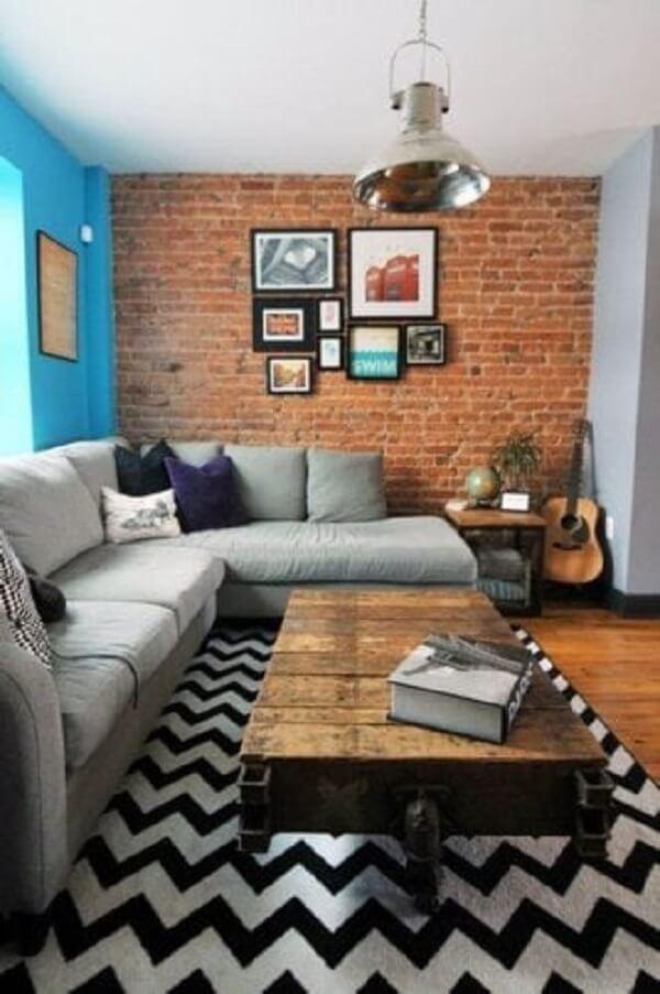 Sala de estar com parede tijolinho e tapete preto e branco chevron