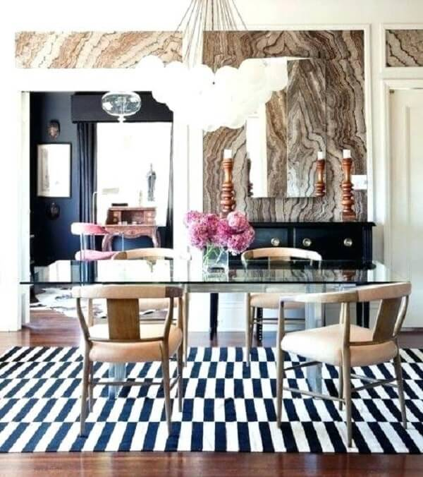 Sala de jantar com mesa de vidro e tapete preto e branco listrado