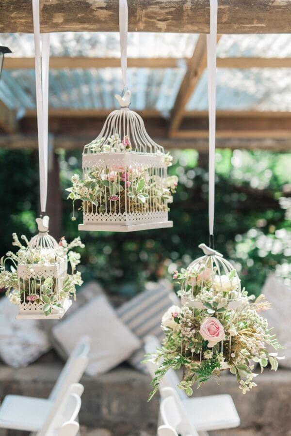 Gaiolas suspensas com flores complementam a decoração da festa de casamento