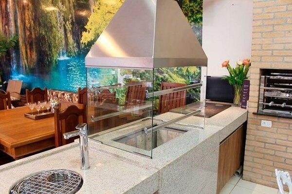 Terraço gourmet com churrasqueira de vidro instalada sobre uma bancada de granito