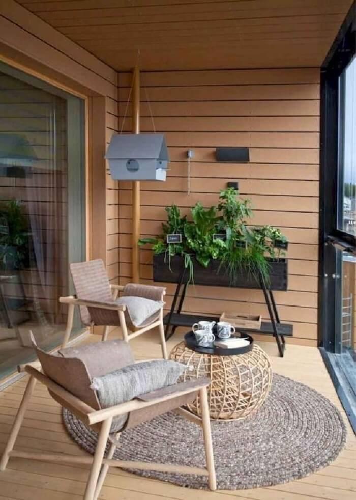 Varanda de madeira com cortina de vidro e jardineira