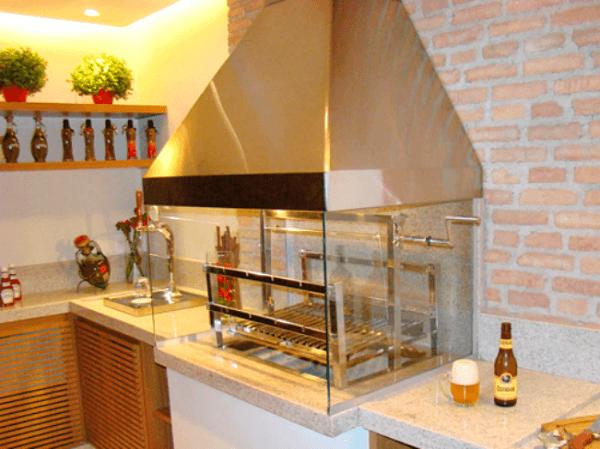 Varanda gourmet com armários de madeira, bancada de granito e churrasqueira de vidro