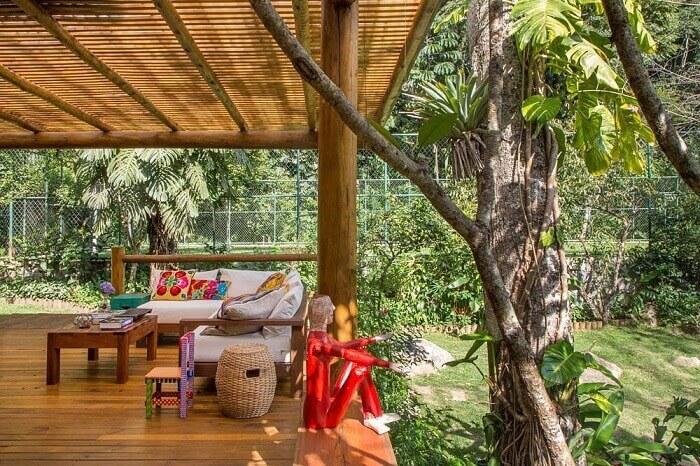 Varanda de madeira com almofadas e outros itens decorativos coloridos