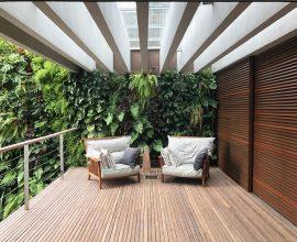 Varanda de madeira com jardim vertical e poltronas