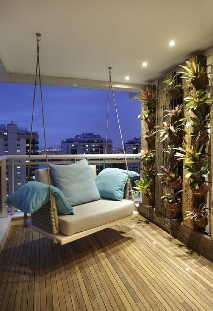 Varanda de madeira com jardim vertical formado por bromélias