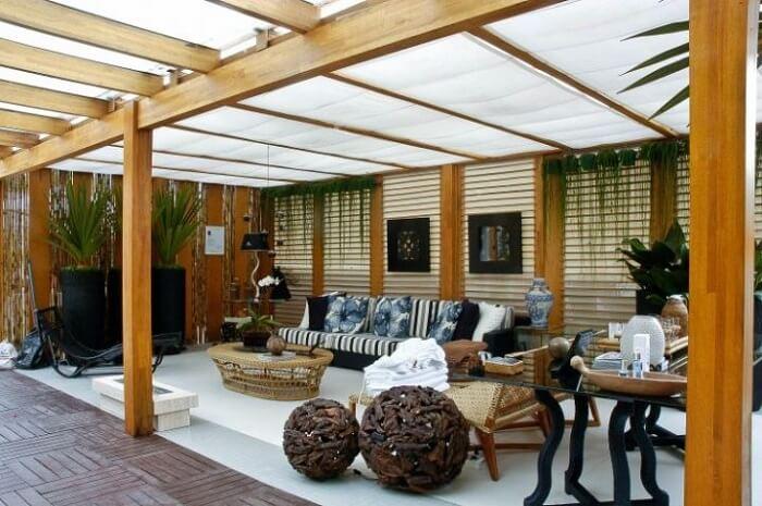 Varanda de madeira com pergolado e móveis rústicos