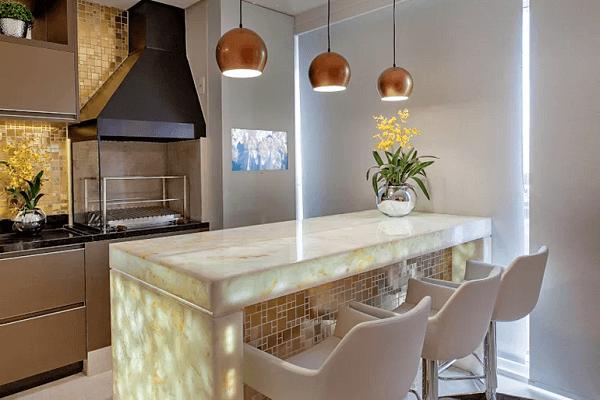 Varanda gourmet com bancada de mármore iluminada e churrasqueira de vidro