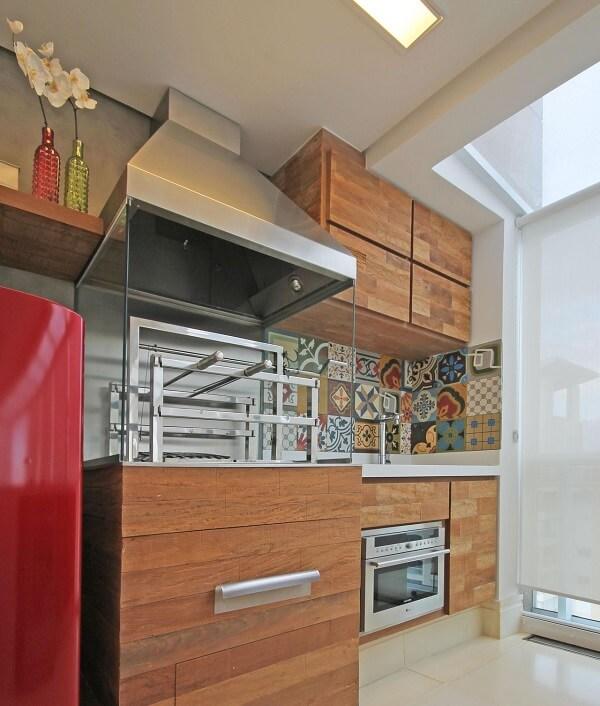 Varanda gourmet com ladrilho na pia e churrasqueira com lateral de vidro e coifa de inox