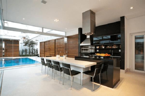 Varanda gourmet integrada a área da piscina com churrasqueira de vidro e bancada preta