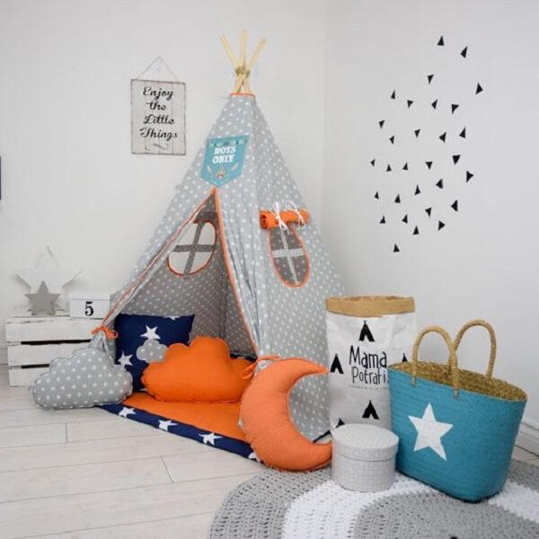 A cabaninha infantil em tons de cinza, laranja e azul se destacam em meio a decoração do quarto