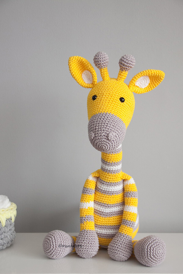 Girafa em tons de amarelo e cinza feita com a técnica de amigurumi