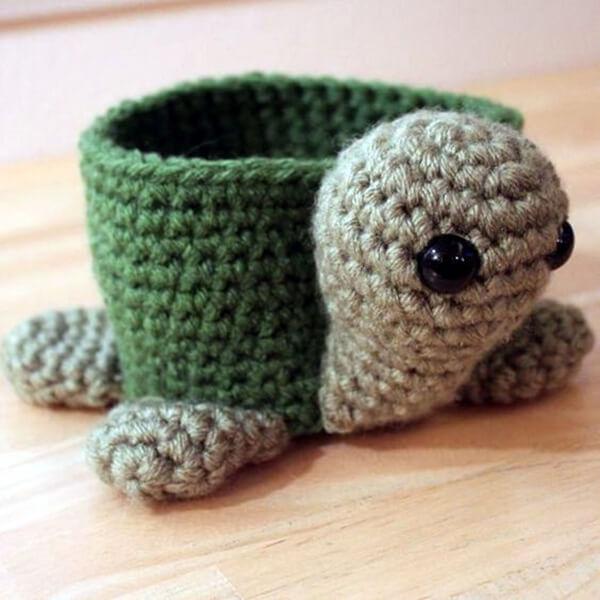Tartaruga de amigurumi serve de suporte para vasinhos