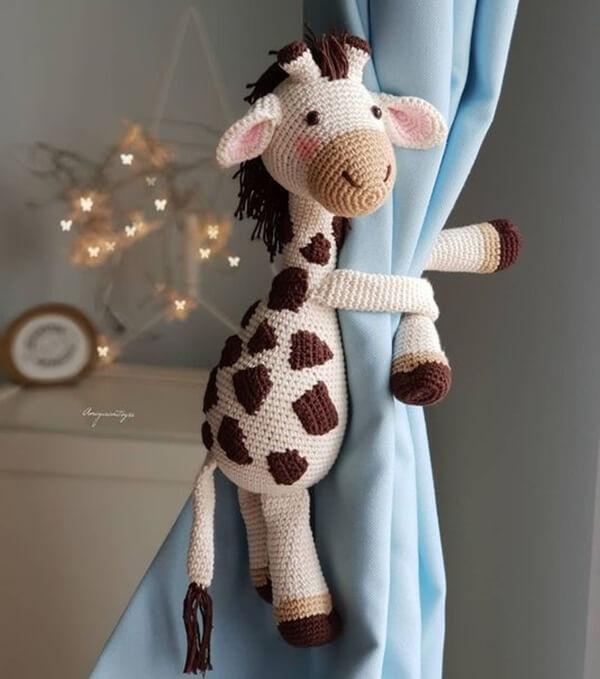 Amigurumi na decoração infantil em forma de prendedores de cortina de girafa