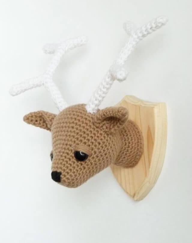 Enfeite de parede com base de madeira e animal feito com a técnica de amigurumi