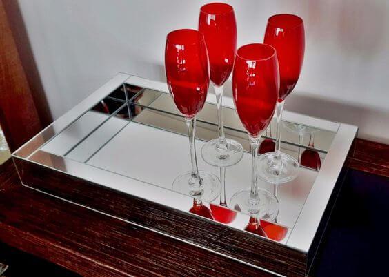 Bandeja espelhada para aparador com taças vermelhas na decoração
