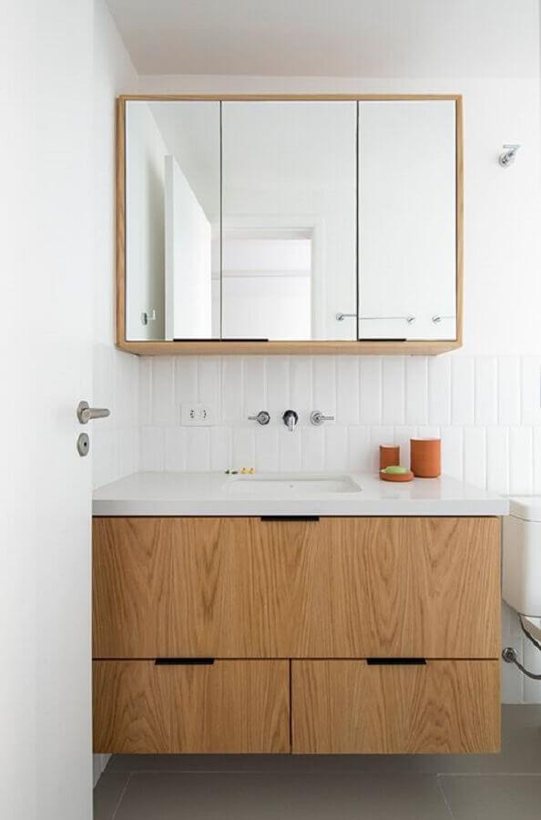 banheiro branco decorado com armário de banheiro de madeira suspenso Foto INÁ Arquitetura