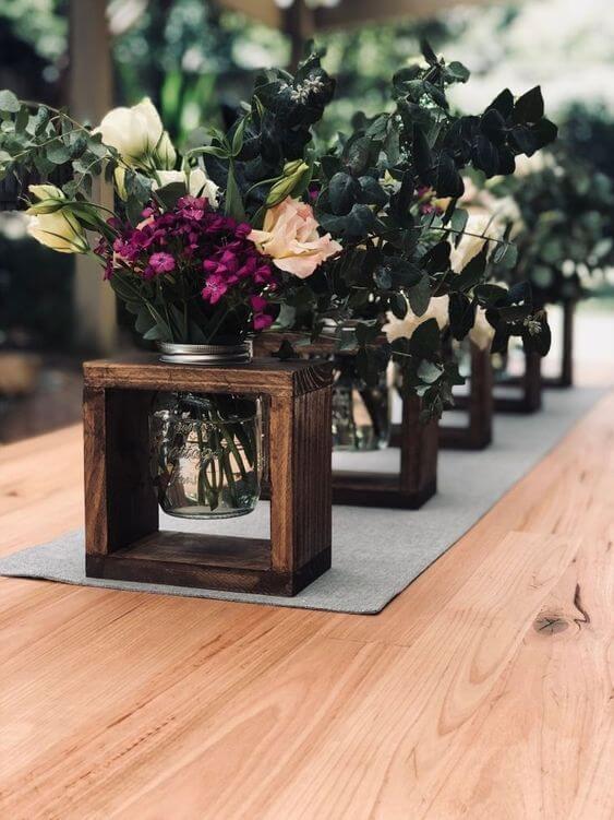 Centro de mesa com vaso de flores com detalhes em madeira
