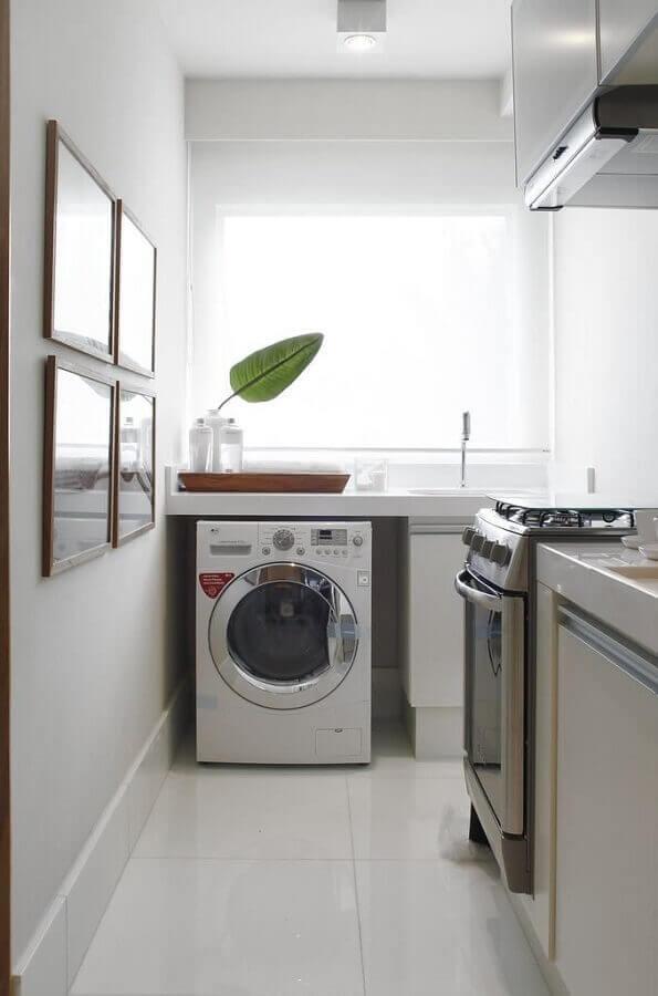 cozinha integrada com área de serviço decorada com cores claras e máquina de lavar e secar Foto Revista VD