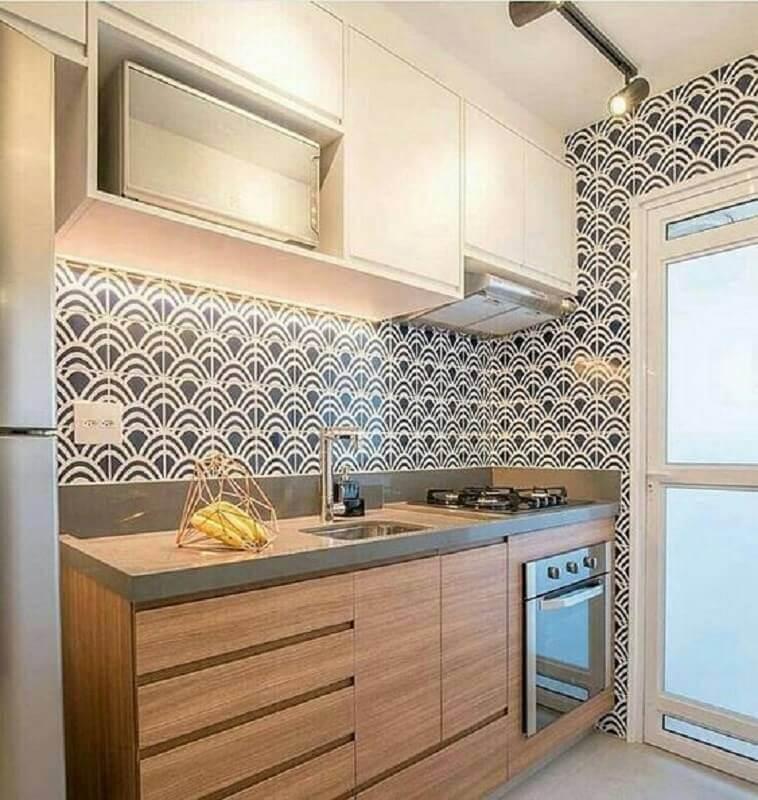 cozinha pequena decorada com revestimento preto e branco e gabinete de cozinha planejado de madeira Foto Jeito de Casa