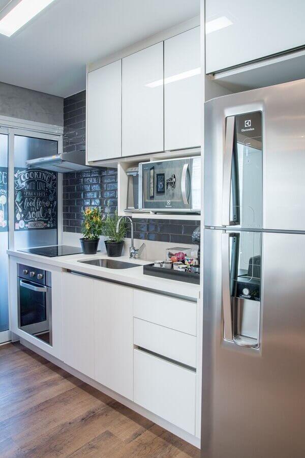 cozinha pequena decorada com revestimento preto e gabinete de cozinha com pia e cooktop Foto Jeito de Casa