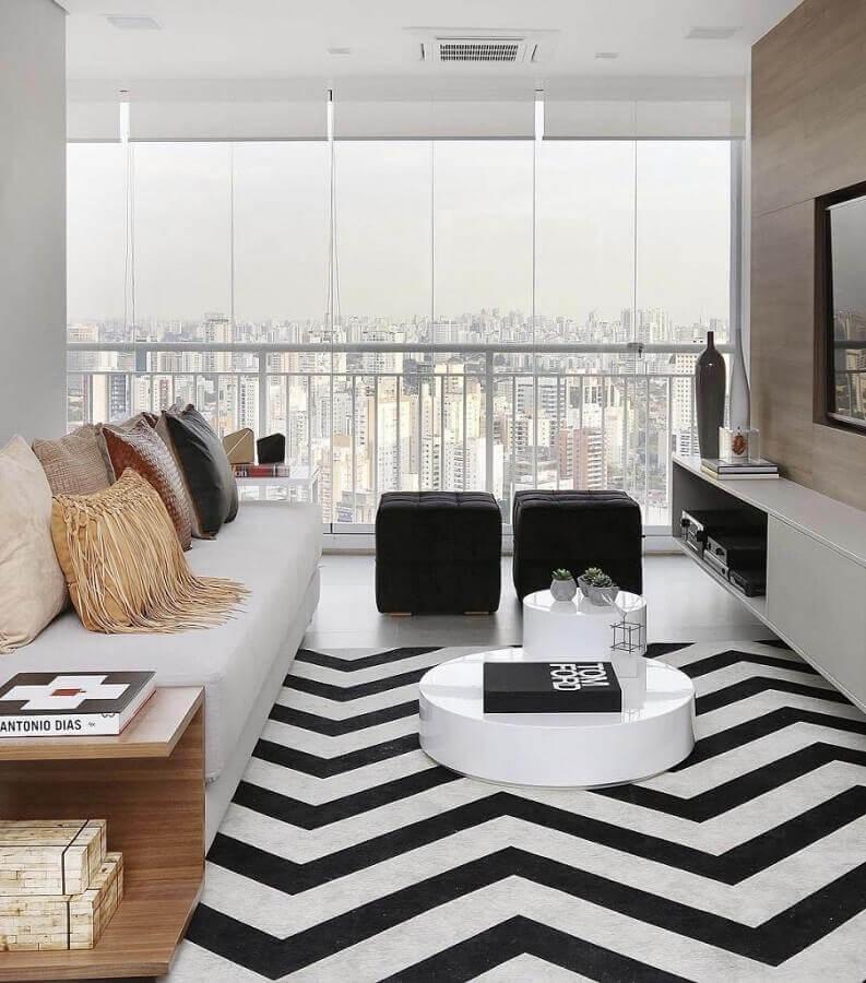 decoração em preto e branco para sala com puff preto e sofá branco de couro Foto Reedcore