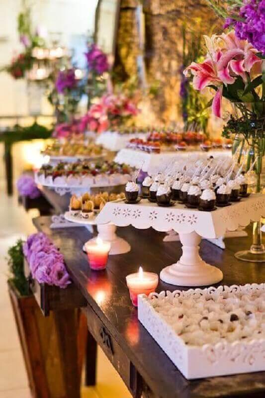 decoração roomantica com arranjo de flores e pratos de bolos branco para mesa de guloseimas Foto Assetproject