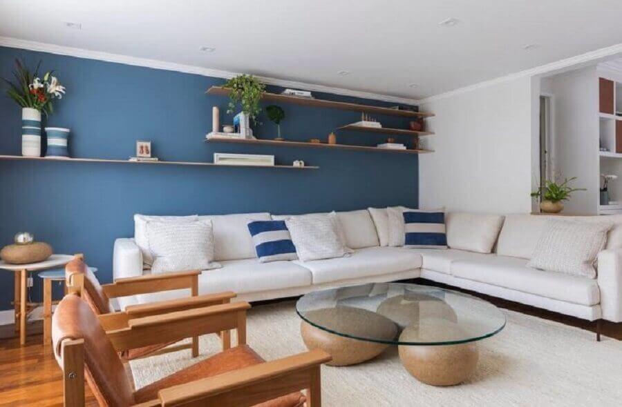 decoração sala ampla com parede azul sofá de canto branco e mesa de centro com base diferente Foto Voa Arquitetura