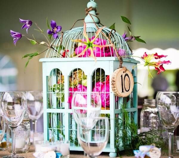 Gaiolas decorativas enfeitam o centro da mesa dos convidados