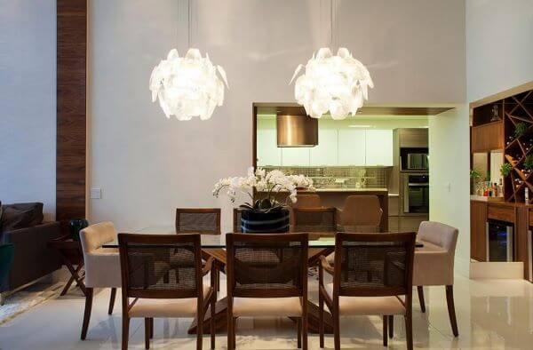 Mesa de jantar de vidro com lustres na decoração
