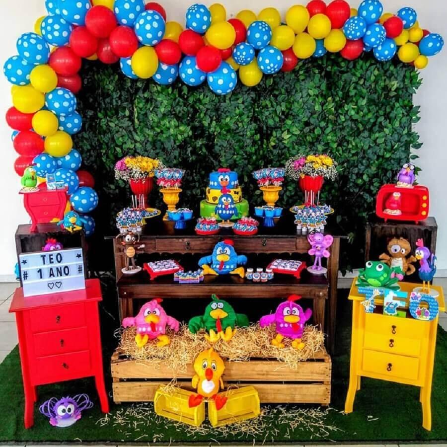 festa da galinha pintadinha simples decorada com painel de folhagens e balões coloridos Foto Navire Festas Decoração