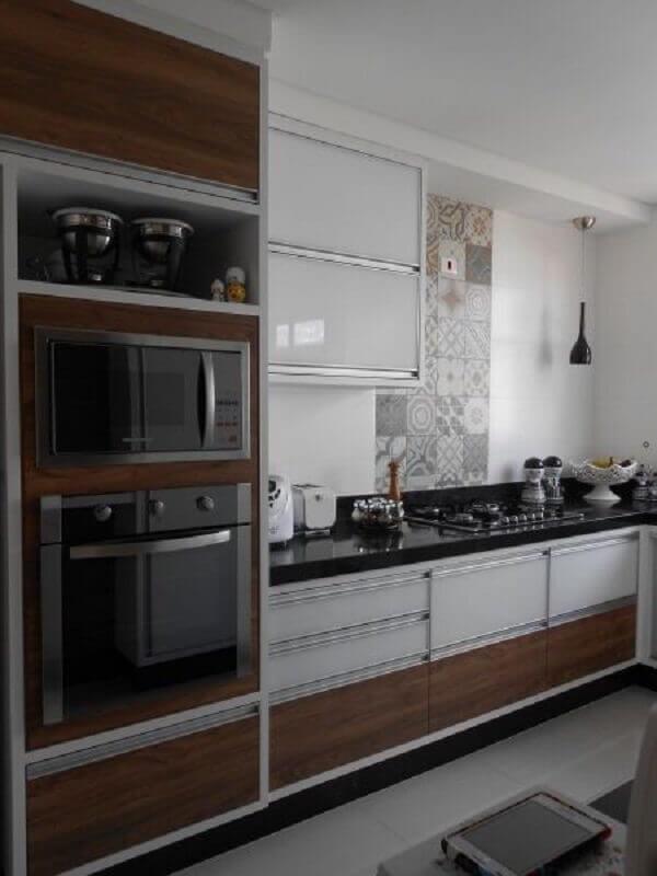forno elétrico embutir para cozinha planejada com armários brancos e detalhes em madeira Foto Pinosy